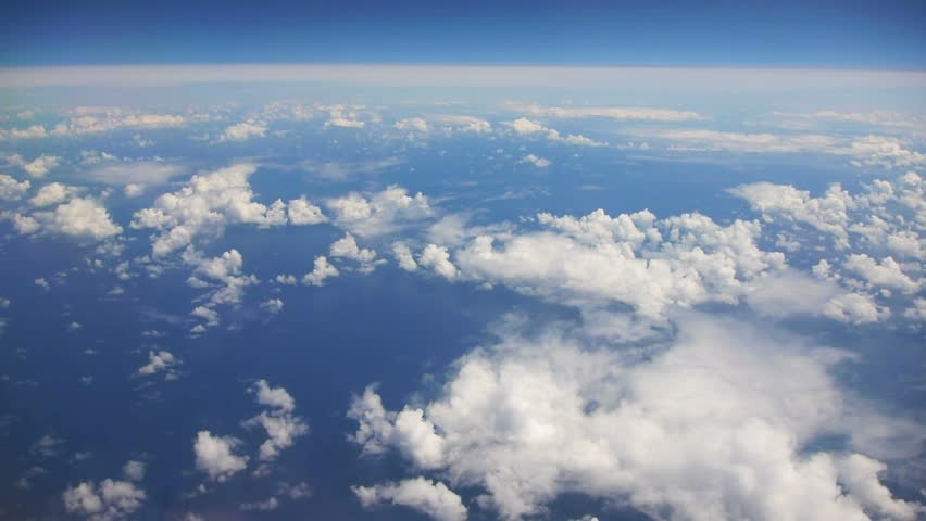Flying in airplane over Pacific ocean and clouds showing Earth's atmosphere.