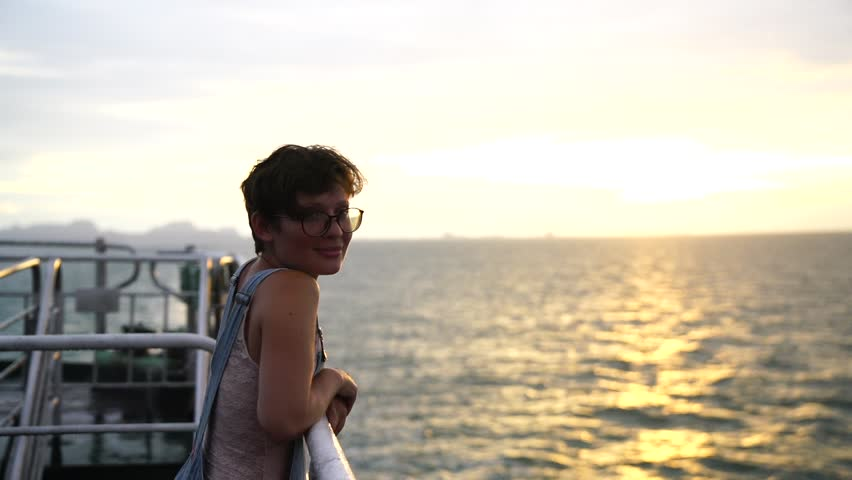 beautiful young girl with short hair wearing glasses and overalls posing at the camera standing on the deck of the ship. sea sunset background.