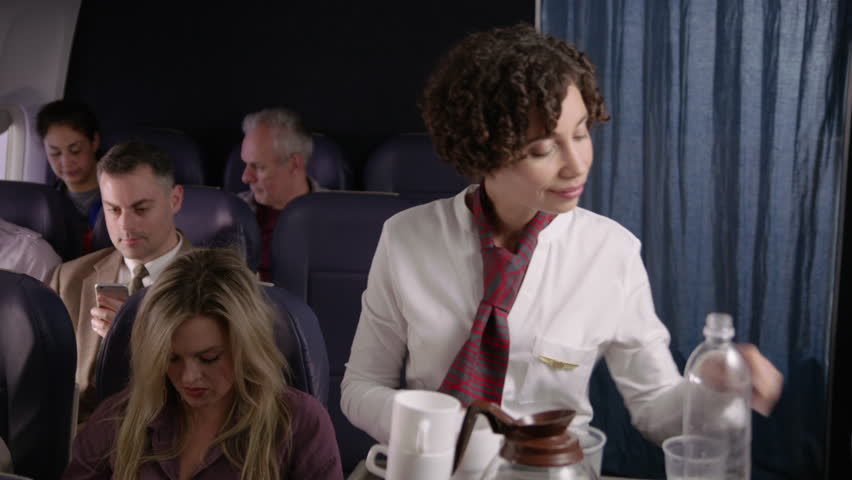 Flight attendant serving drinks and snacks to airliner passengers