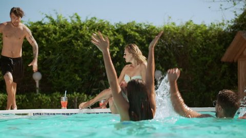 Blonde Caucasian female in sunglasses sitting near pool while her friends jumping into water splashing smiling laughing playing. In slowmotion