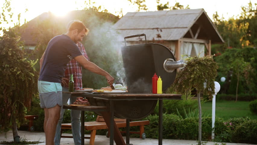 Two Caucasian males making hamburgers with fried meat and buns near barbecue grill in slowmotion