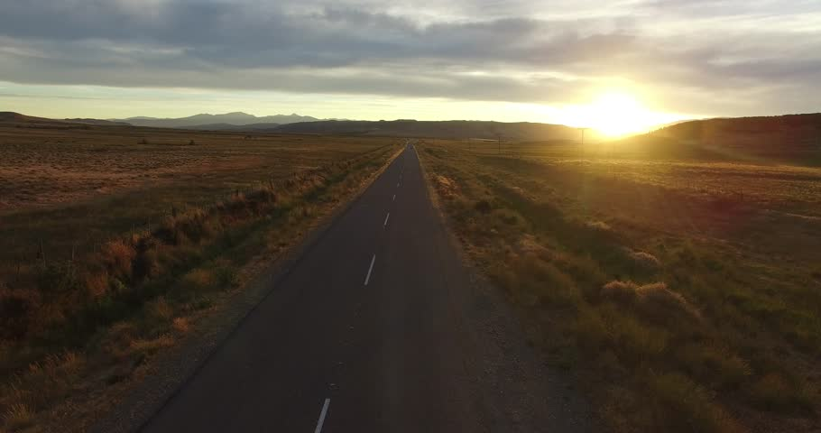 Aerial drone scene at sunset golden hour of route in steppe. Mountains on the background. Camera flying over road. Desert rural landscape, Patagonia Argentina.