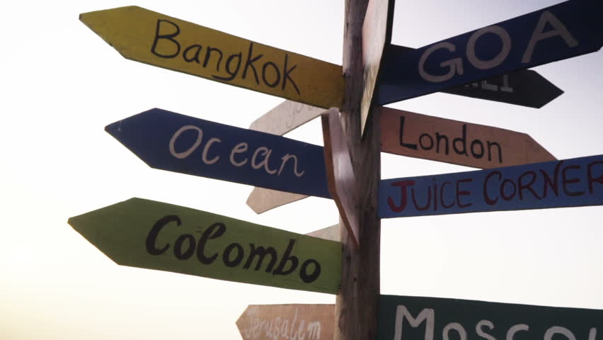 a wooden traffic sign pointing to various cities and directions