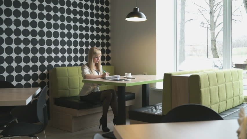 Model girl sitting in a cafe writes important information in a daily log #23063620