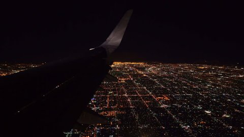 Aerial view from airplane window over Los Angeles City Lights on approach to landing at airport