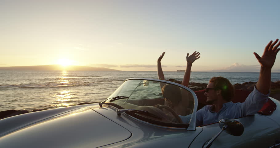 Happy Couple Driving on Country Road By the Ocean into the Sunset in Classic Vintage Sports Car. Hands in the Air. Shot on RED