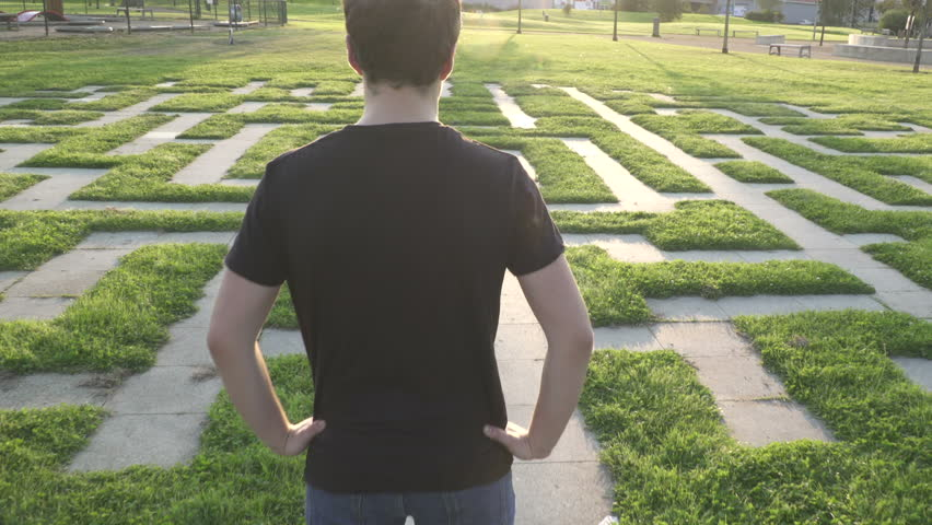 Camera fly from A teen-age  boy looking around a life-size Labyrinth  It shows thoughtfulness before choosing the life path Illustrate life Labyrinth and teenager's choice. Released