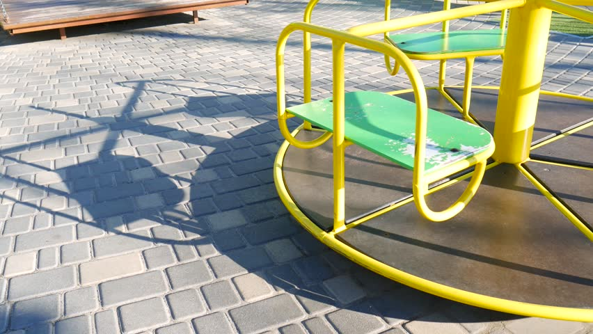 Roundabout merry go round spinning on empty playground with its shadow