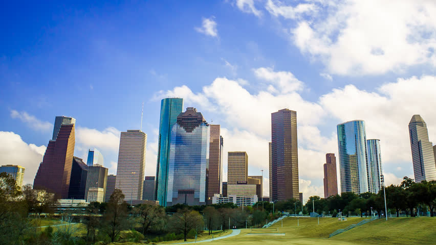 Houston Texas Clouds Time Lapse 4K 1080p. A time-lapse of Houston skyline with clouds rolling over buildings and blue skies. Shot from a park with grass and trees