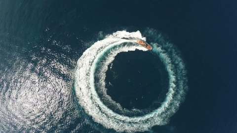 Perpendicular aerial view of a maxi rib designing a circle in the sea navigating fast