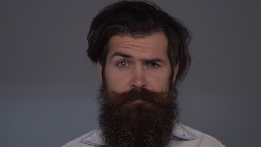 Slow motion: Surprised man raises eyebrows. Bearded man with emotional eyebrows and dark hair