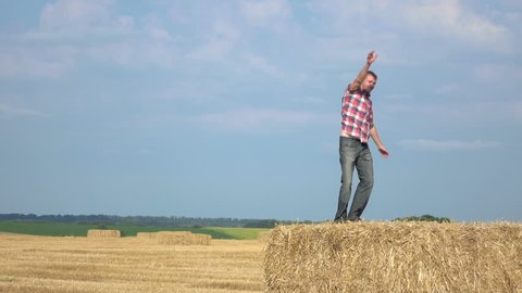 Young farmer is dancing on the hay in the field.