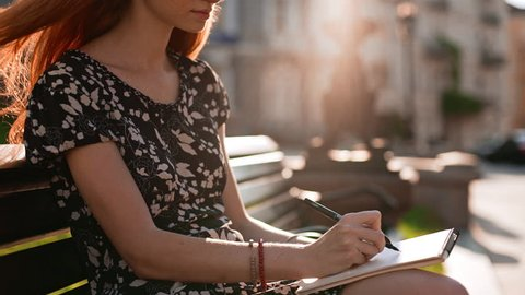 Thoughtful young redhead girl in black and white dress with pen and notebook looking down in slowmotion