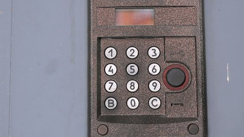 Person pushing the buttons on the panel of the intercom outdoors