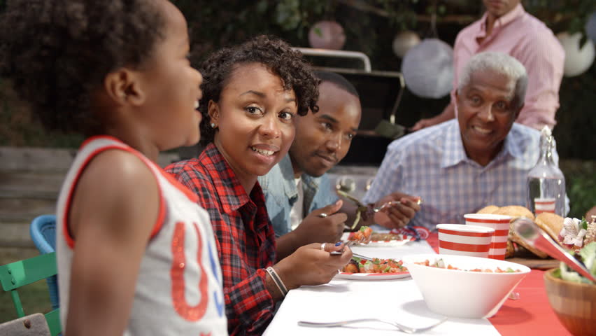 Two young black boys stand to entertain family at a barbecue