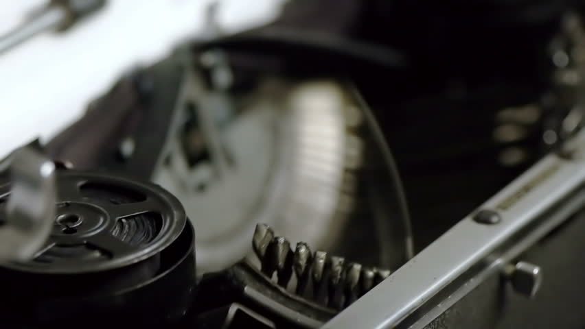 Typing on Vintage Typewriter (HD). Typing on Vintage 1940s typewriter seen from an angle with shallow depth of field ink roll seen moving. Ambient audio Included.