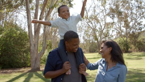 Parents with son on dad's shoulders having fun in the park