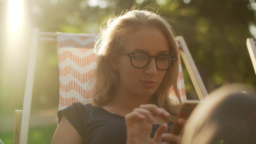 Blonde Caucasian female with glasses sitting on lounge in park with mobile phone smiling speaking in slowmotion | Shutterstock HD Video #23239537