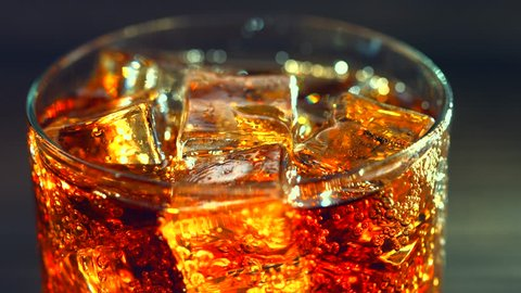 Cola with ice cubes on wooden table. Cola with Ice and bubbles in glass. Soda closeup. Food background. Cola pouring into a glass, dolly shot 4K UHD video footage. Ultra high definition 3840X2160