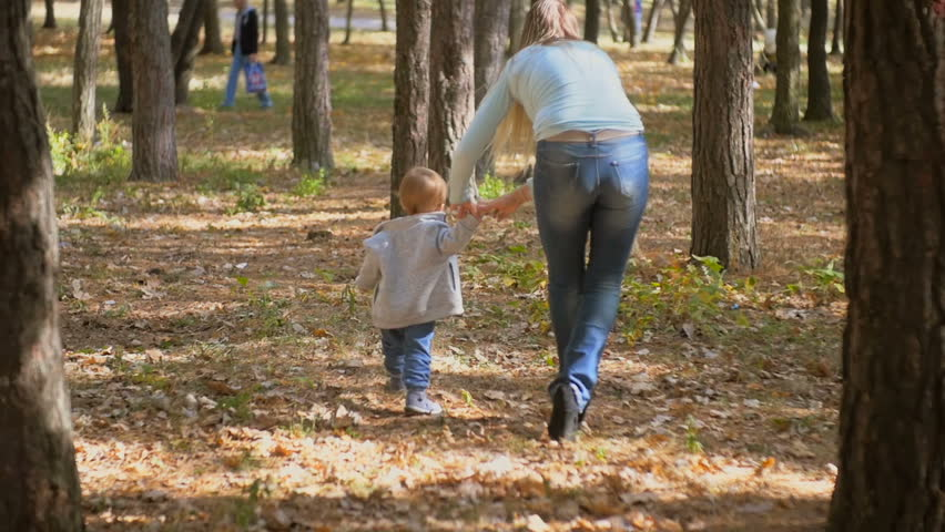 Slow motion footage of young mother walking with her baby son at autumn park #23286457