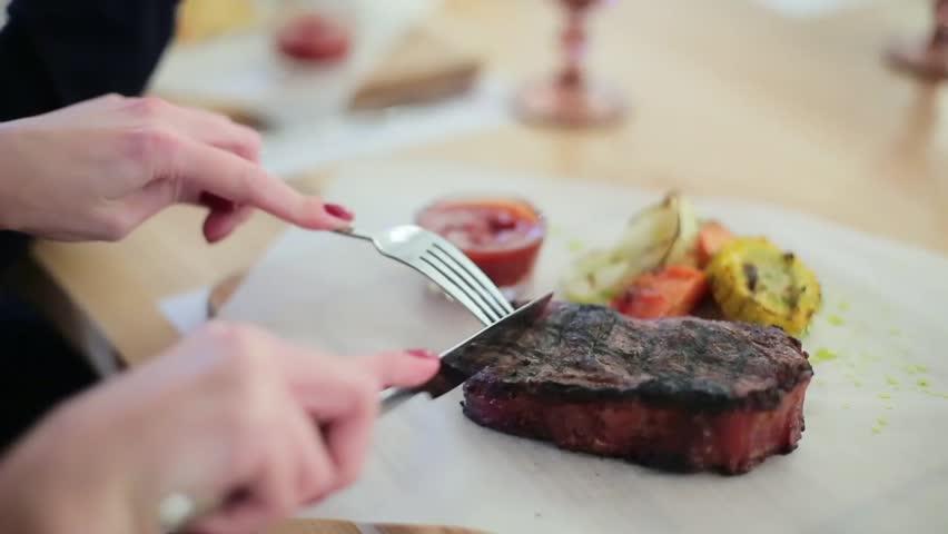 girl cuts a steak in a restaurant.