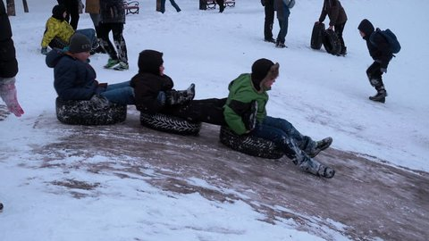 Kiev/Ukraine Jan 2017.  Entertainment teens winter in a city park. Extreme skiing on the ice slides. Three boys riding on tires as a train. Children will quickly move down the hill on the icy hill.