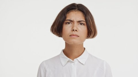 Young beautiful brunette east asian female in shirt looking suspiciously at camera showing disapproval with two thumbs on white background