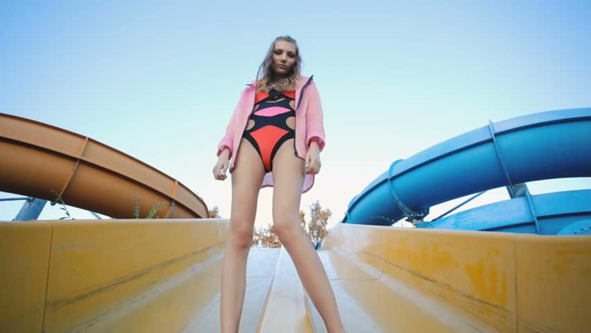 Beautiful young girl dressed in a swimsuit posing in an abandoned aquapark at summer evening,