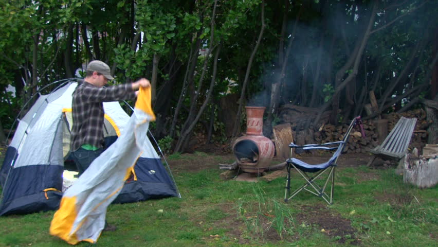 Man sets up campsite with tent and makes fire in backyard with his pet cats interested in the activity.