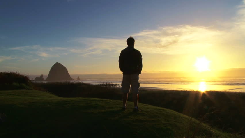 Man at Pacific Ocean near Cannon Beach looks out to sea as sun sets on beautiful day.