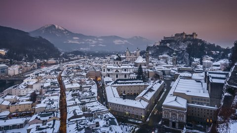 Day to night time-lapse footage of the historic city of Salzburg with famous Festung Hohensalzburg and Salzach river illuminated in beautiful twilight during scenic Christmas time in winter, Austria.