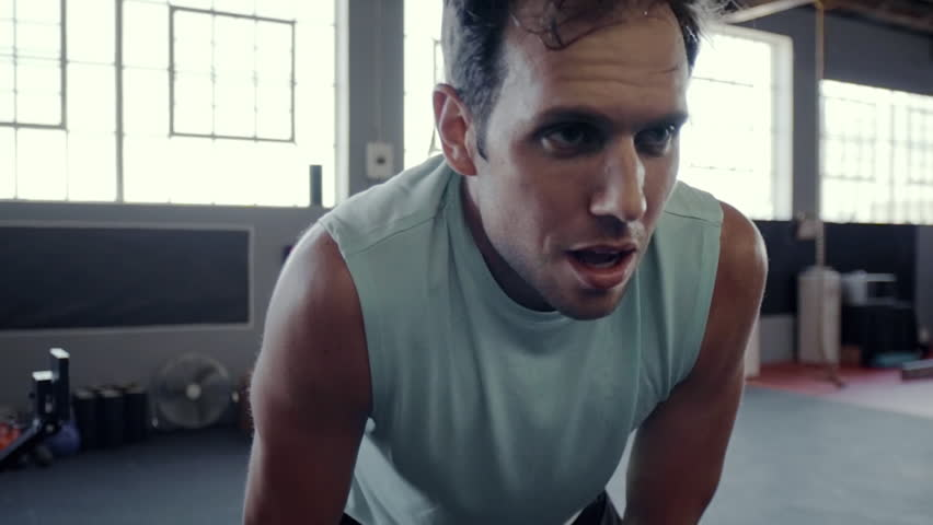 Unfit gym man struggling to keep up with high intensity workout
