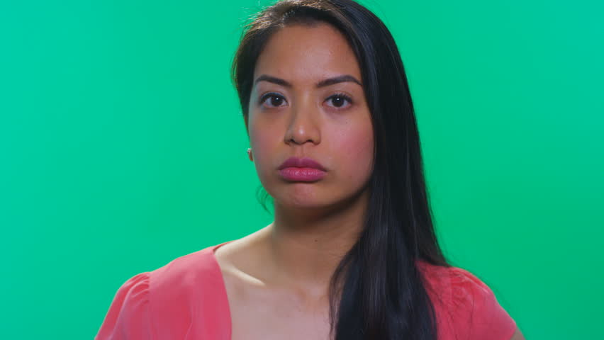 Asian woman on green background rolling her eyes | Shutterstock HD Video #23399527