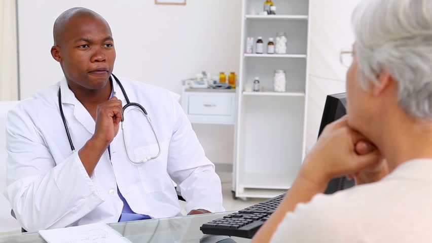 Happy doctor talking with his patient in a medical office