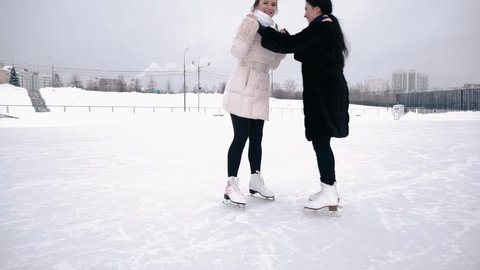 Two young women skating on ice rink in a park. They are moving toward camera