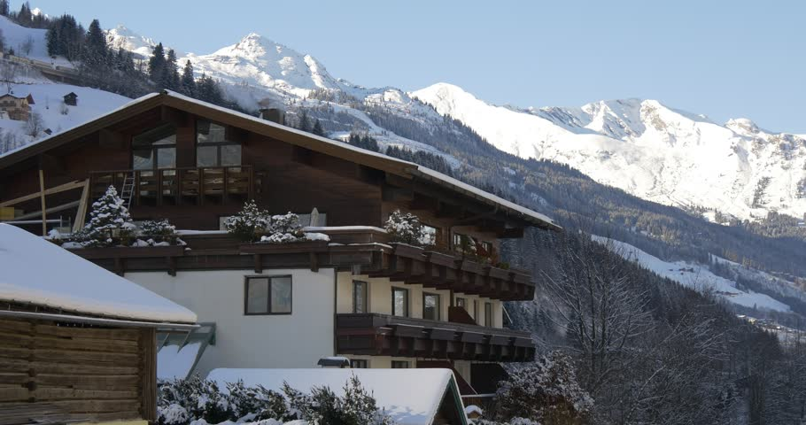 Typical Alpine hotel in the winter with mountains in the background #23437837