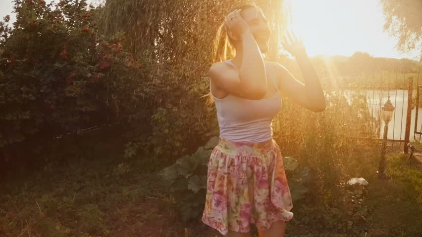 Slow motion footage of laughing young woman dancing under summer rain at sunset