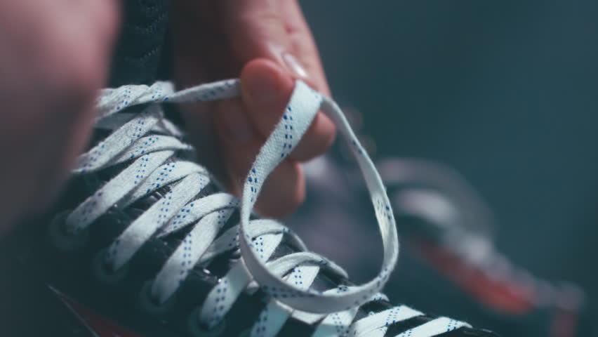 EXTREME CU Caucasian ice hockey player tightening laces on his skates in the locker room, preparing for the game. 4K UHD 60 FPS RAW edited footage | Shutterstock Video #23454109