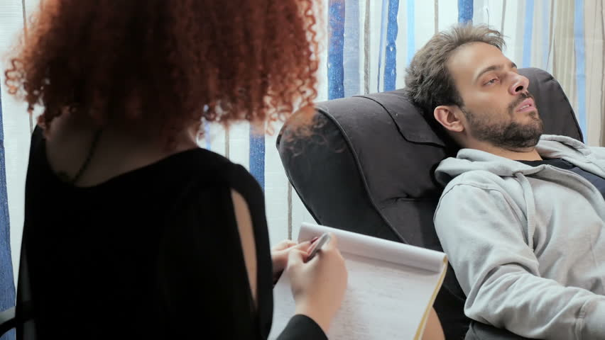 Psychologist talks to the patient lying on the couch | Shutterstock HD Video #23462617
