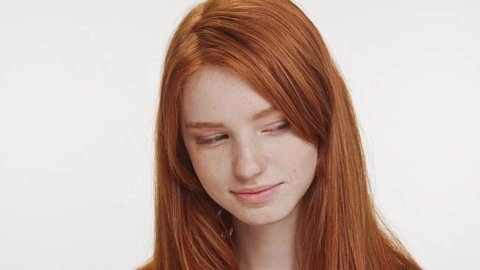 Shy charming ginger Caucasian teenage girl looking at camera lightly smiling. Close up footage on white background in slowmotion