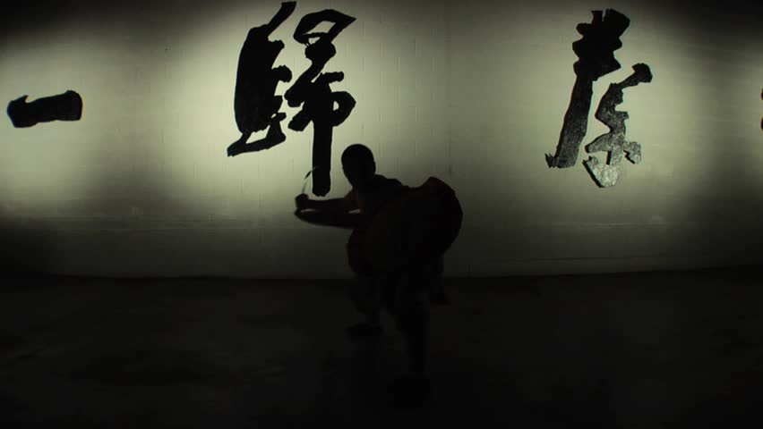 A Shaolin monk demonstrates in silhouette an ancient form of kung fu using a practice sword and shield. Shot in slow motion.