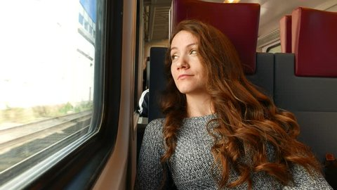 Calm woman travel in modern comfortable train, ride to airport. Brunette lady look out of window with faint smile, flickering sunlight, carriage pass by under bridge. Passenger portrait, enjoy journey