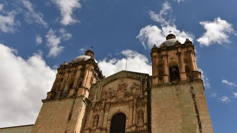 Cathedral of Santo Domingo in Oaxaca, Mexico, front of the church with two steeples and clouds that run behind the blue sky, time lapse