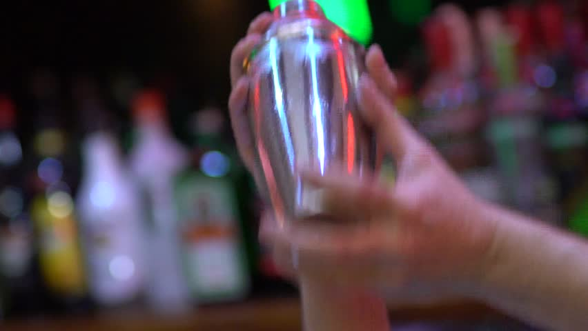SLOW MOTION: Close up shot of a bartender shaking a drink in a cocktail shaker.