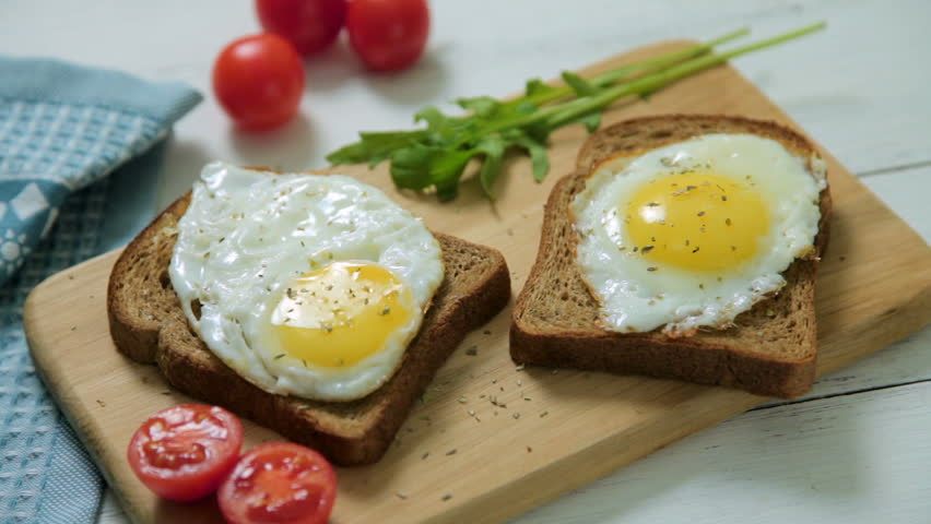 Healthy Breakfast: scrambled eggs on slices of whole-grain bread with arugula and tomatoes on a wooden Board