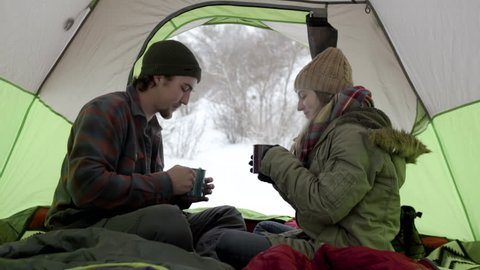 Couple Warm Up (On Winter Camping Trip) With Steaming Hot Cocoa,They Cheers And Carefully Sip