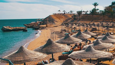 EGYPT, SOUTH SINAI, SHARM EL SHEIKH, DECEMBER 3, 2016: Beach umbrellas and sunbeds in Egypt on the Red Sea. The coastal resort line, where people relax and sunbathe. Landscape for relaxation.