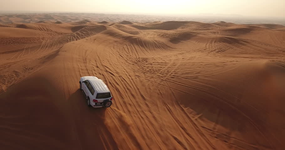 DUBAI, UAE - JANUARY 3, 2017: Aerial view of jeep driving in desert at sunrise. A desert safari is peculiar to Dubai and the UAE. A trip that lasts a couple of hours as you move through the sand dunes #23574487
