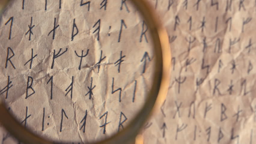Vintage magnifying glass and runic random letters