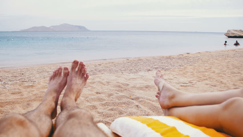 Legs of People Lying on Beach Sun Lounger near the Sea. Couple man and woman lie on the loungers at the sandy beach in Egypt, overlooking the Red Sea. Young couple relaxing in the chaise lounge